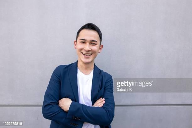 porträt eines jungen geschäftsmannes, der auf einer einfachen grauen wand steht - japanischer abstammung stock-fotos und bilder