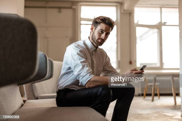 portrait of young businessman using cell phone in a loft - hoofd schuin stockfoto's en -beelden