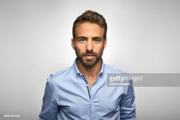 portrait of young businessman wearing blue shirt - vollbart stock-fotos und bilder