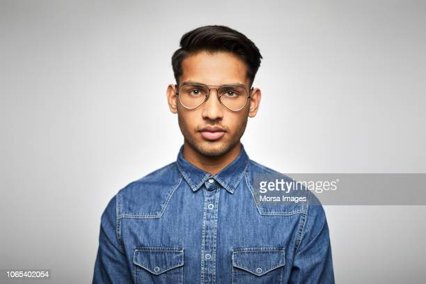 portrait of young businessman wearing eyeglasses - cultura hindú fotografías e imágenes de stock
