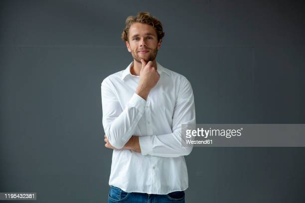 portrait of young businessman, wearing white shirt - hand on chin stock pictures, royalty-free photos & images