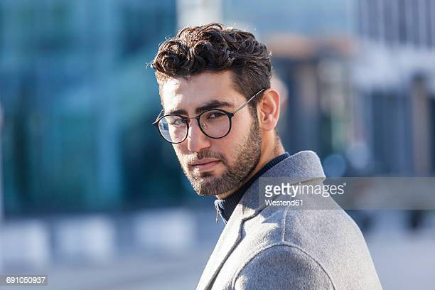 portrait of young businessman with beard and spectacles - tourner photos et images de collection
