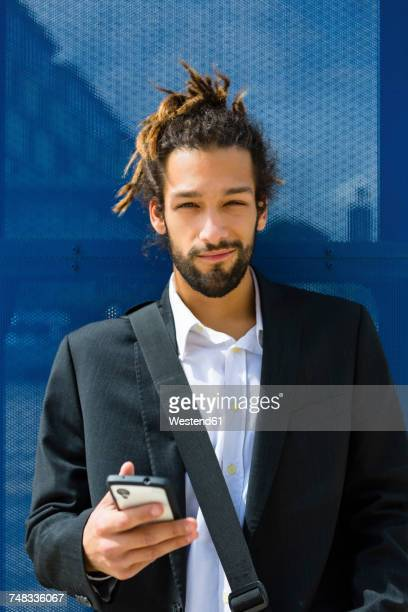 Portrait of young businessman with dreadlocks using smartphone