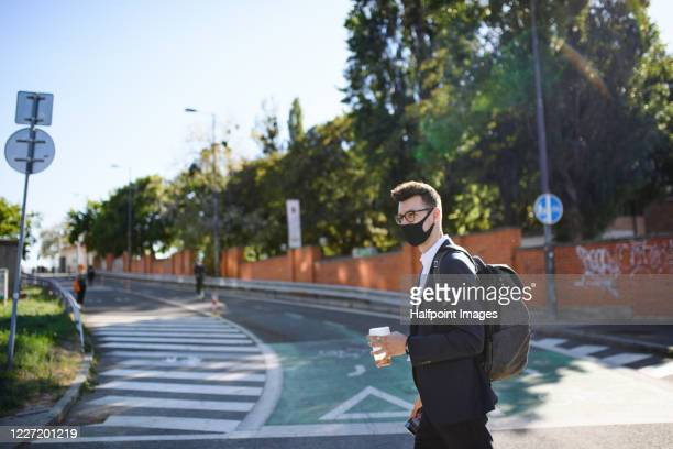 portrait of young businessman with face mask and coffee walking in city, crossing the road. - pedestrian stock pictures, royalty-free photos & images