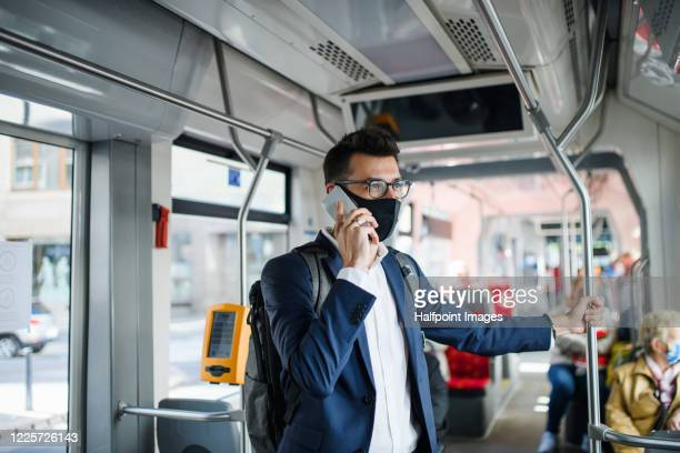portrait of young businessman with face mask using smartphone in public transport, travelling to work. - transport stock pictures, royalty-free photos & images