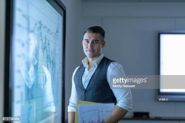 portrait of young businessman with interactive screen with graphs and charts in business meeting - monty rakusen stock pictures, royalty-free photos & images