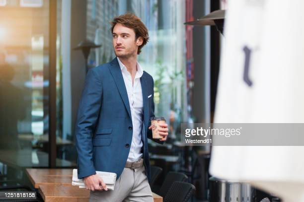 portrait of young businessman with newspaper and coffee to go outdoors - giacca da abito foto e immagini stock