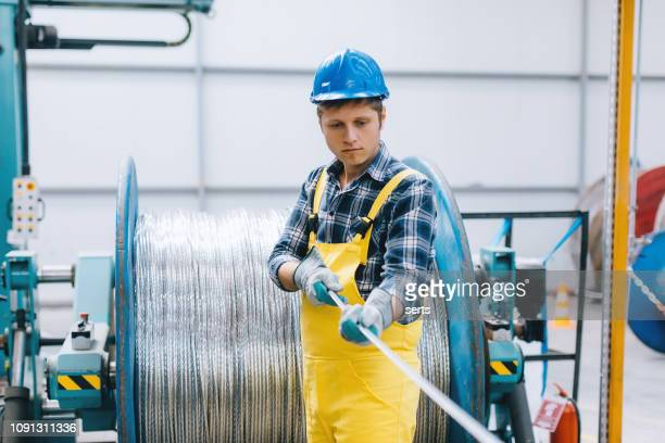 portrait of young businessman working with cable roll in factory - cavo d'acciaio foto e immagini stock