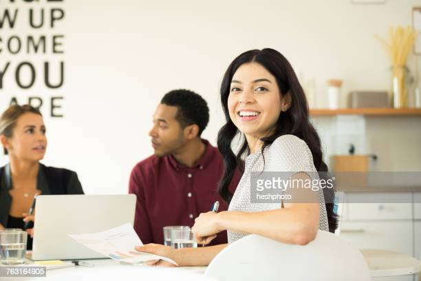 portrait of young businesswoman at conference table meeting - heshphoto stock pictures, royalty-free photos & images