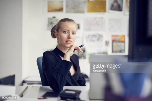 Portrait of young businesswoman at desk in the office