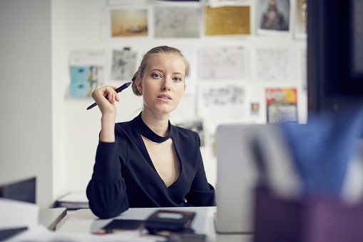 Portrait of young businesswoman at desk in the office - gettyimageskorea