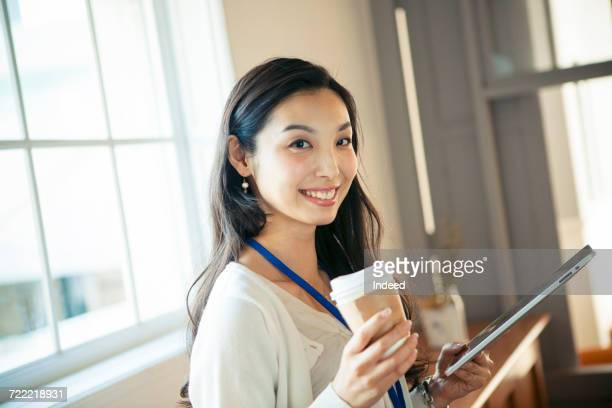 portrait of young businesswoman, holding digital tablet and coffee cup - japanese ol ストックフォトと画像