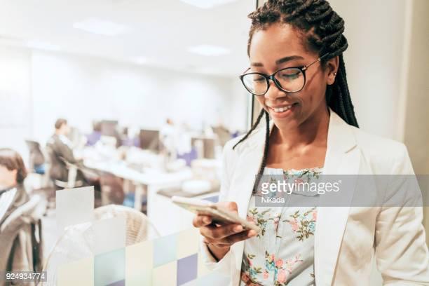 Porträt der jungen Unternehmerin halten Handys in Kreativbüro