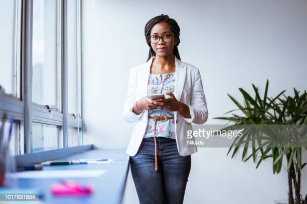 Porträt der jungen Unternehmerin halten Handys im Büro