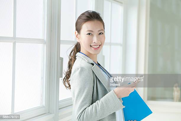 Portrait of young businesswoman holding mobile phone