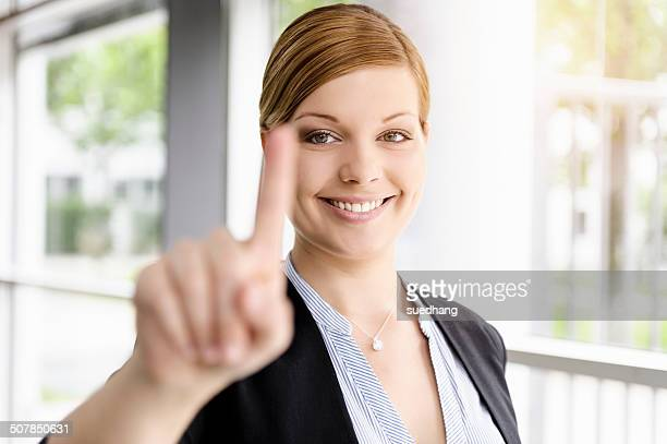 Portrait of young businesswoman holding up a finger