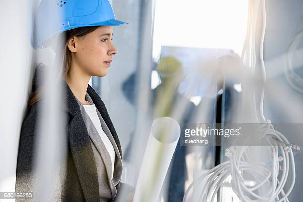 Portrait of young businesswoman in new office behind power cables