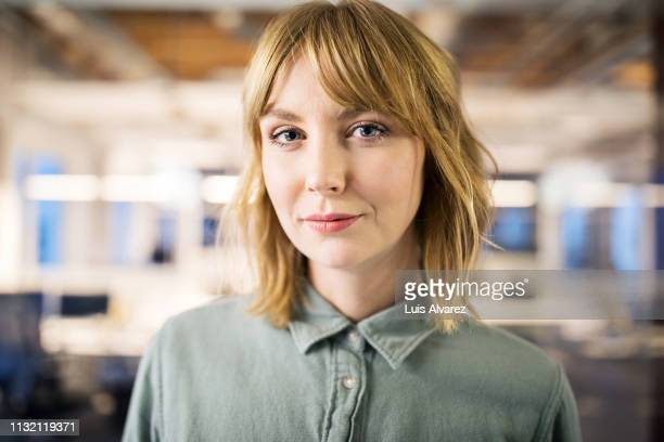 portrait of young businesswoman in office - mulheres imagens e fotografias de stock