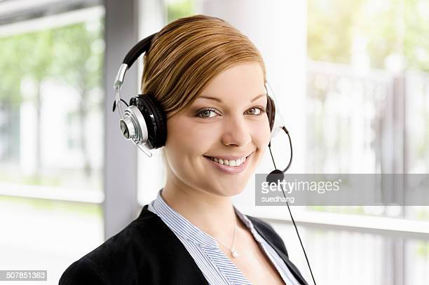 Portrait of young businesswoman in telephone headset