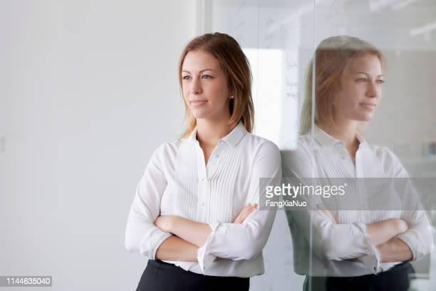 portrait of young businesswoman leaning against glass wall - rolled up sleeves stock pictures, royalty-free photos & images