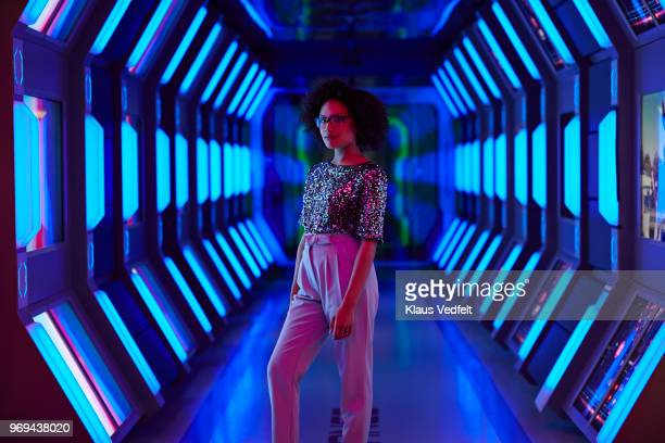 portrait of young businesswoman looking in camera in spaceship like corridor - dreiviertelansicht stock-fotos und bilder