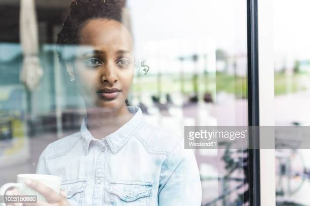 portrait of young businesswoman looking out of window, holding coffee cup - spiegelung stock-fotos und bilder