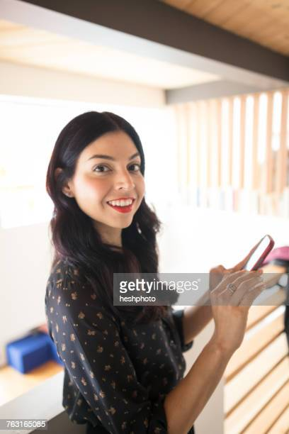 portrait of young businesswoman on balcony with smartphone - heshphoto stock pictures, royalty-free photos & images
