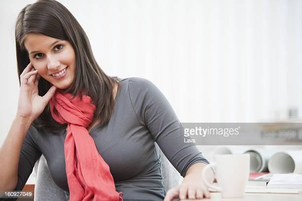 portrait of young businesswoman sitting at desk with cup