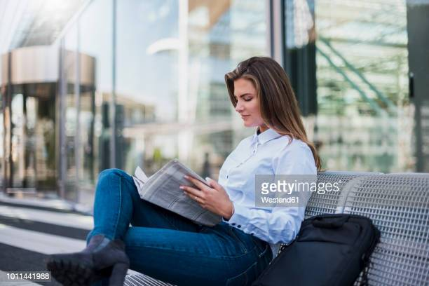Portrait of young businesswoman sitting on bench reading newspaper