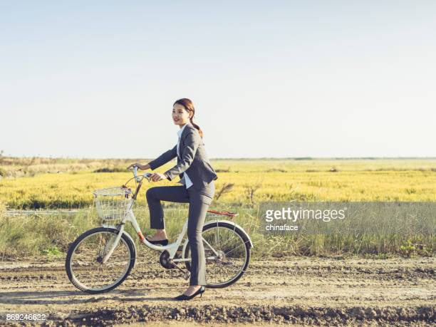 portrait of young businesswoman sitting on bicyale at countryside