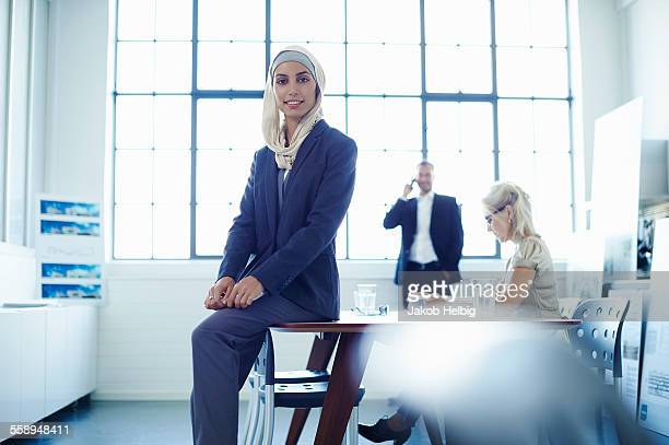 Portrait of young businesswoman sitting on office desk
