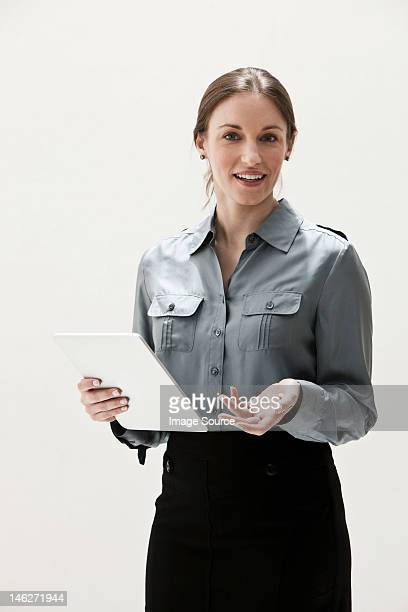 Portrait of young businesswoman smiling and using digital tablet, studio shot