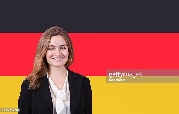 Portrait of young businesswoman smiling over German flag
