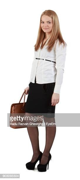 Portrait Of Young Businesswoman Standing Against White Background