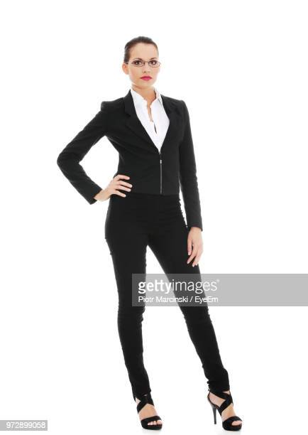 portrait of young businesswoman standing against white background - hand on hip stock pictures, royalty-free photos & images