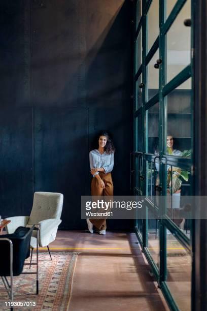 portrait of young businesswoman standing at the window in loft office - una sola mujer joven fotografías e imágenes de stock