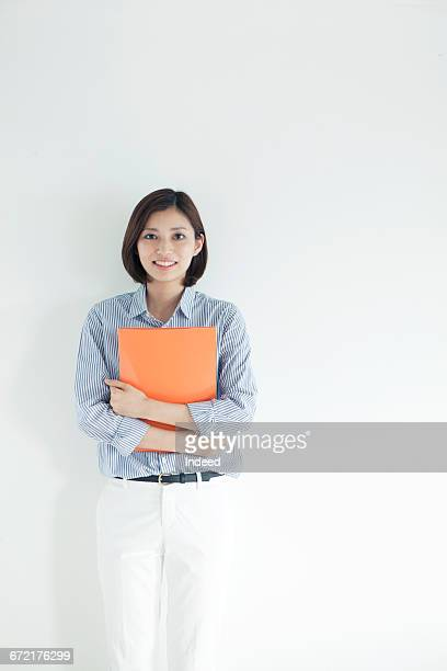 Portrait of young businesswoman standing by wall