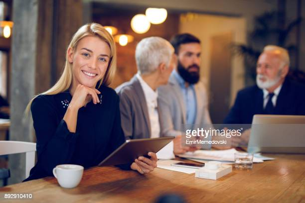 Portrait of young businesswoman using digital tablet in cafe.
