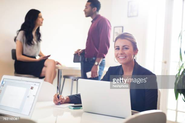 portrait of young businesswoman using laptop at desk - heshphoto stock pictures, royalty-free photos & images