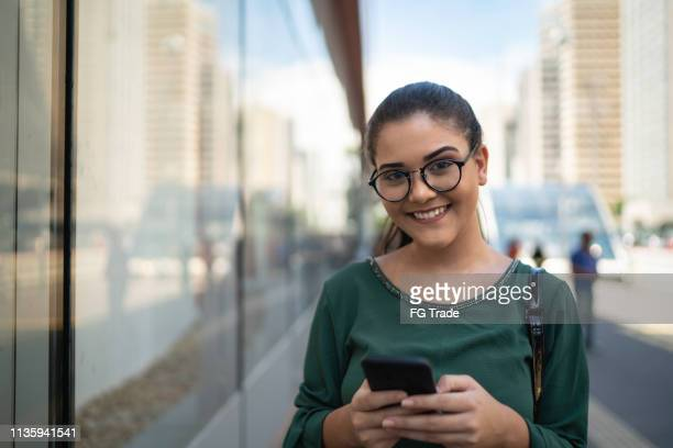 portrait of young businesswoman using mobile at street - 21st century stock pictures, royalty-free photos & images