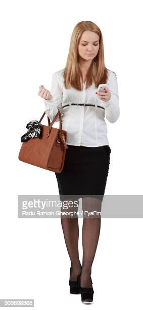 Portrait Of Young Businesswoman Using Mobile Phone Against White Background