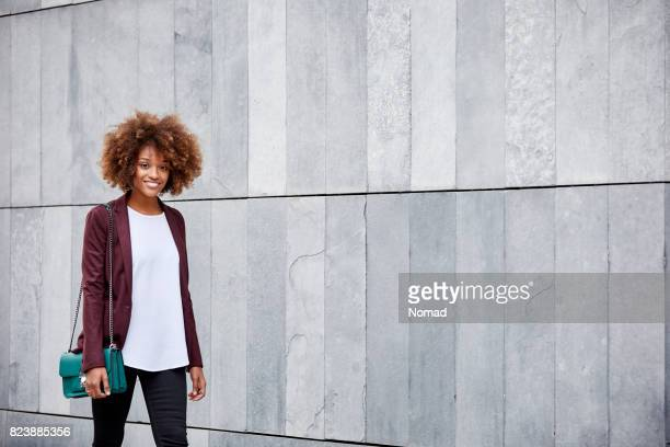 Portrait of young businesswoman walking by wall