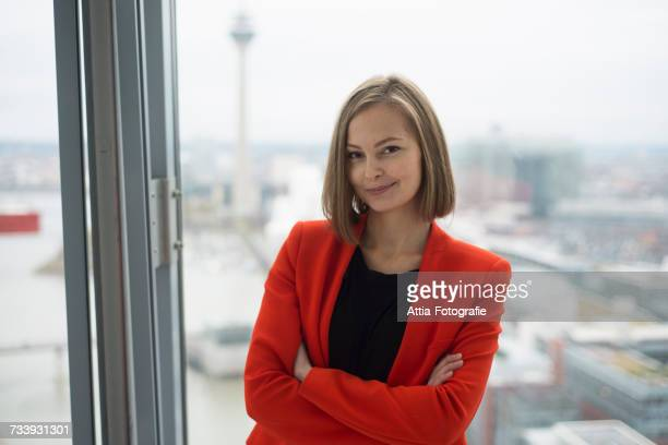 portrait of young businesswoman with arms folded in front of office window - red suit stock pictures, royalty-free photos & images