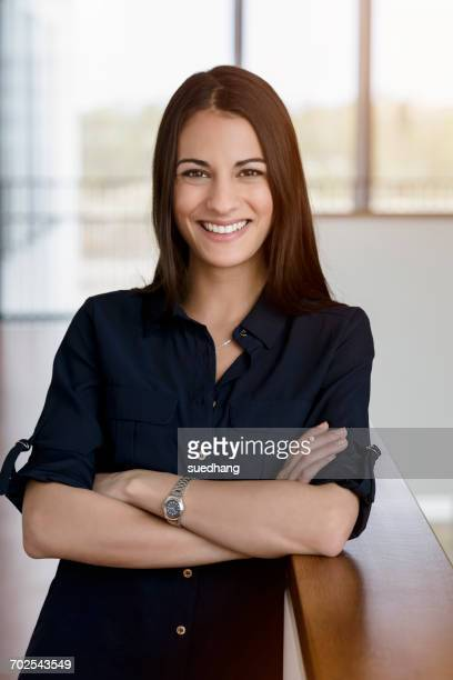 portrait of young businesswoman with arms folded in office corridor - weiblichkeit stock-fotos und bilder