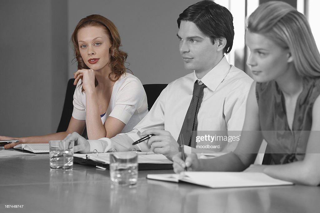 Portrait of young businesswoman with colleagues in a meeting : Stock Photo