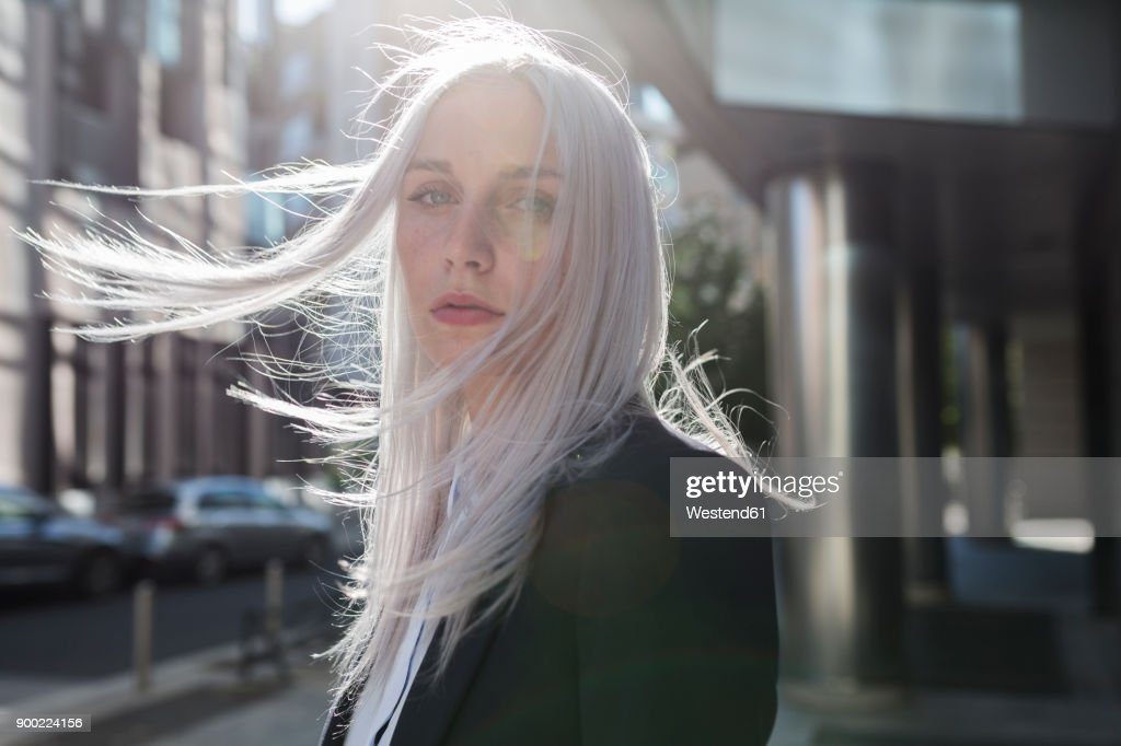 Portrait of young businesswoman with windswept hair in the city : Stock Photo