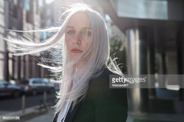 portrait of young businesswoman with windswept hair in the city - graues haar stock-fotos und bilder