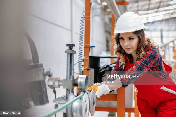 Portrait of young businesswoman working with ball valves in factory