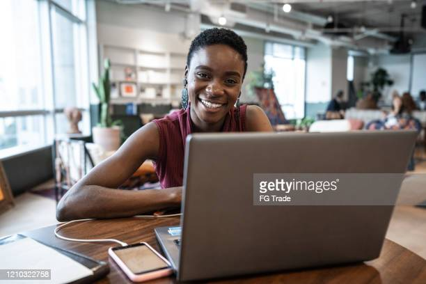 portrait of young businesswoman working with laptop at coworking - founder stock pictures, royalty-free photos & images