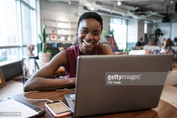 portret van jonge onderneemster die met laptop bij het coworking werkt - oprichter stockfoto's en -beelden